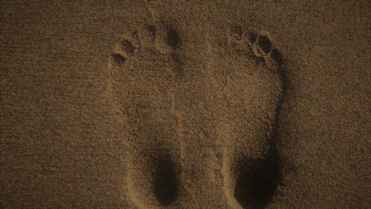 Stopy v písku prezentující metodu zvanou reflexologie.