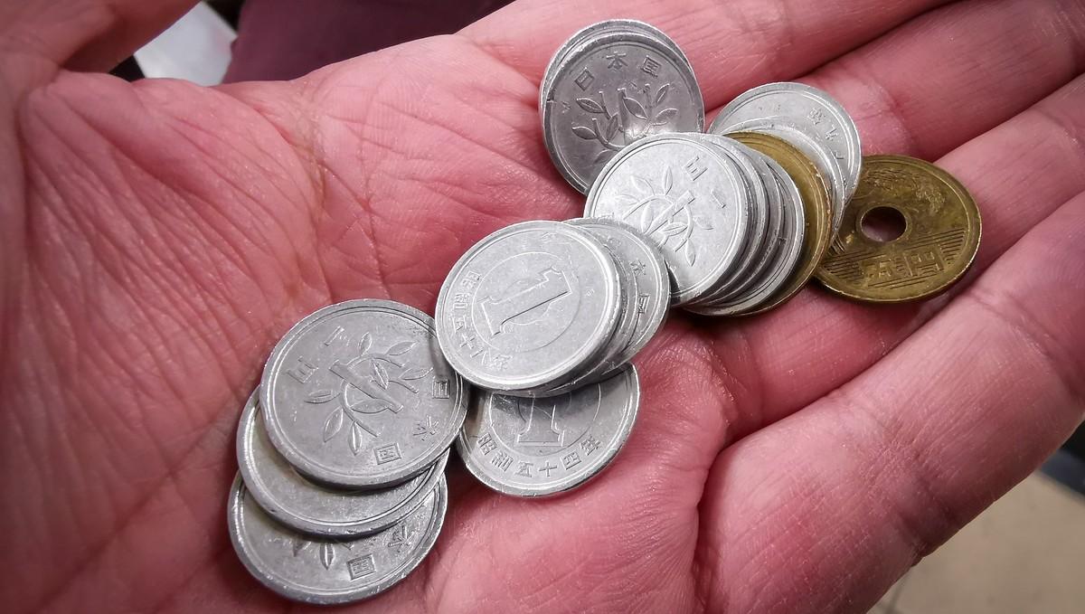 Peníze v ruce symbolizující různé příspěvky.