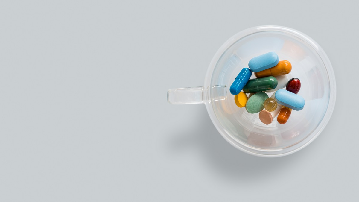 Vitamíny nasypané v malém plastovém kalíšku.